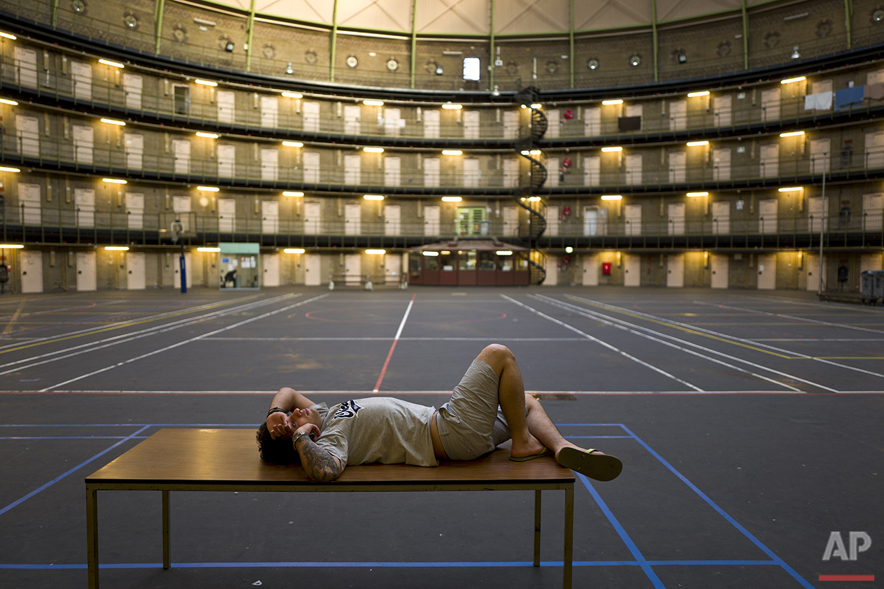 In this Friday, May 6, 2016 photo, Iranian migrant Reda Ehsan, 25, lies on a table at the former prison of De Koepel in Haarlem, Netherlands. (AP Photo/Muhammed Muheisen)