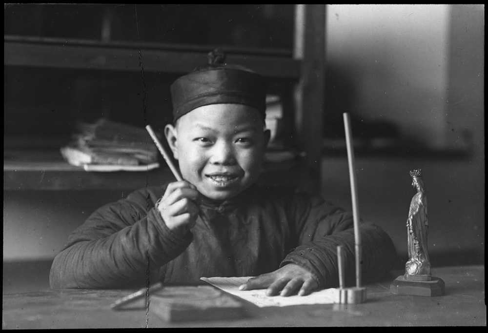 'Smiling boy seated at a table writing'. China, c. 1918-1938.
